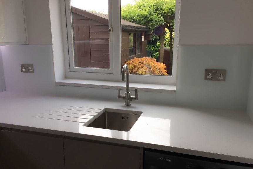 glass-splashback-sat-behind-aluminium-tap-and-sink