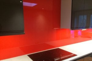 glass splashback over hob coloured in candy red
