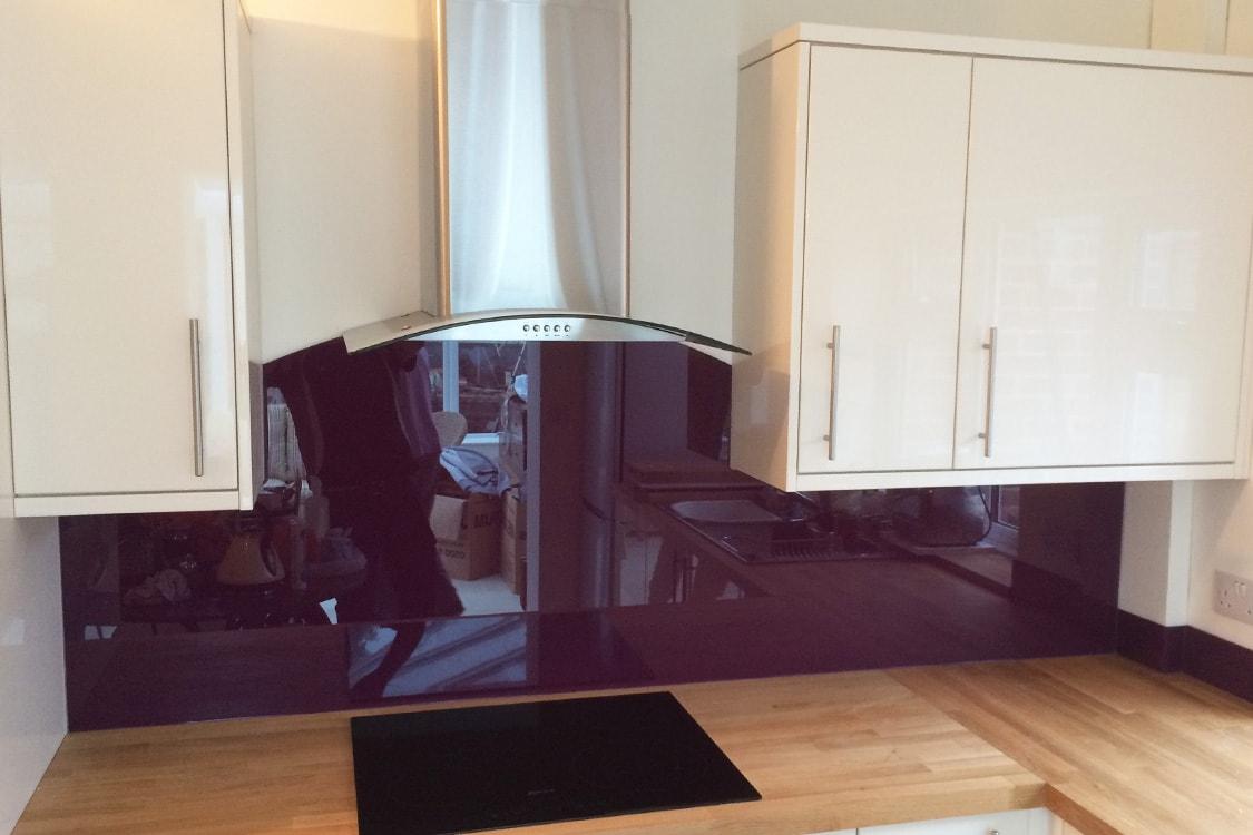 glass splashback with curved cooker hood coloured in purple violet