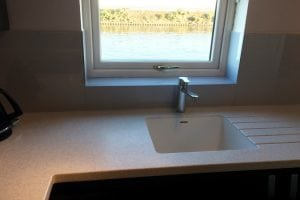 glass splashback and window sill fitted behind sink looking over lake