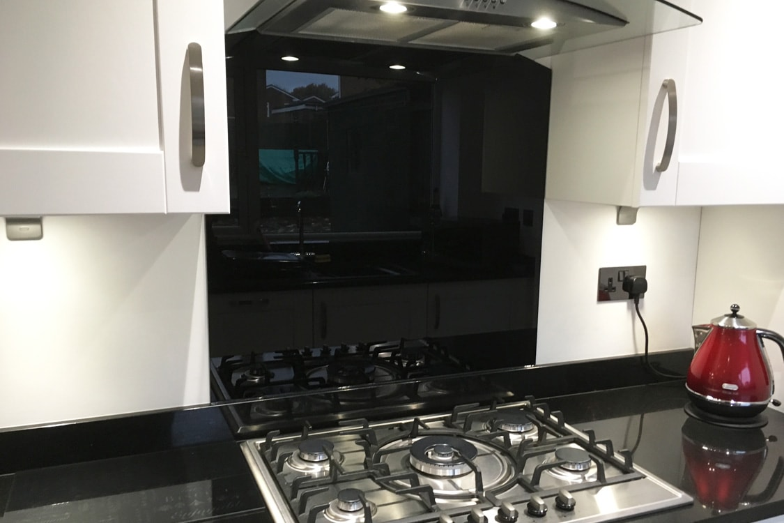 glass splashback with cooker hood cutout in black
