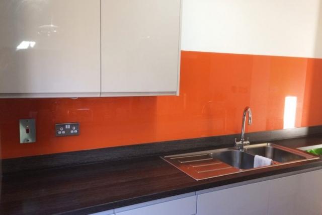 kitchen glass splashback coloured in bright red orange