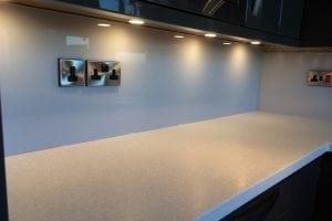 stunning glass splashback fitted under kitchen spotlights