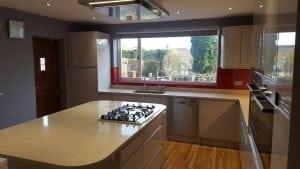 Red Glass Splashback On Top Of White Granite Worktops