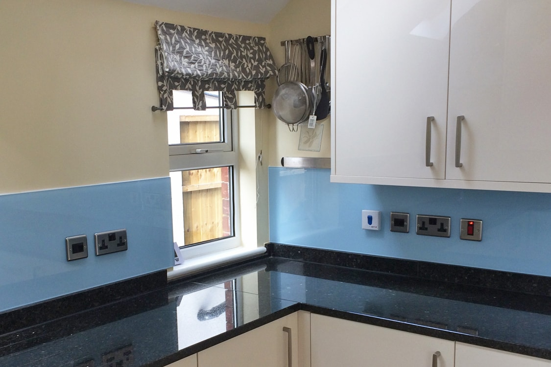 Glass Splashback with Socket Cutouts in Smeg Blue